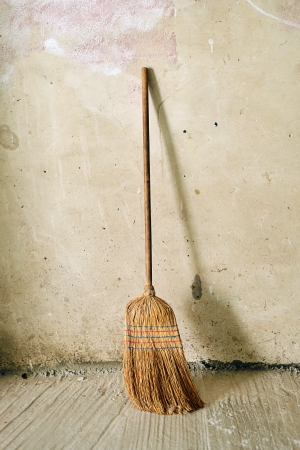 a house with a straw: Old obsolete broom or besom leaning on the gray wall Stock Photo