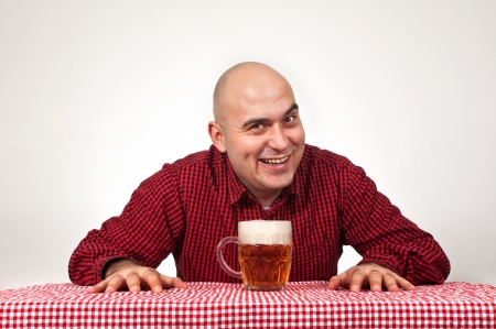 drinker: Bald beer drinker sitting in the bar with a glass of cold lager on the table.