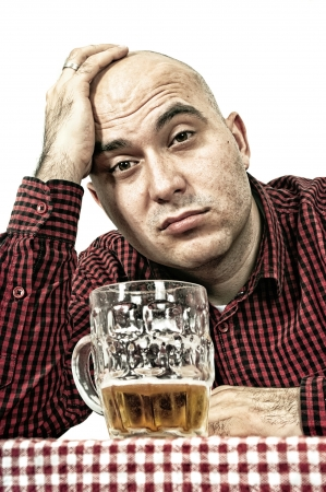drinker: Bald beer drinker sitting in the bar with a glass of cold lager on the table, sad face - depression concept.