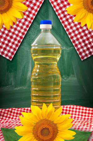 aceite de cocina: Aceite de girasol amarillo en una botella de plástico sobre una mesa de cocina