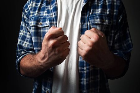 hist: Casual man standing with hist fists clenched in victory, close up  Determination and strength concept