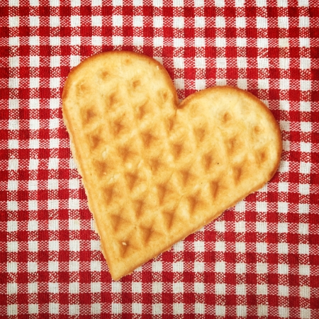Heart shaped galette cookie on red and white checkered table cloth  photo