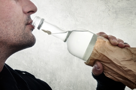 Man is drinking vodka from the bottle, alcoholism concept. photo