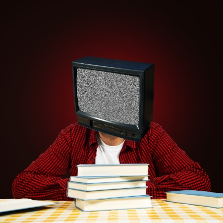 Young adult bold student with TV head and few books sitting at the table. photo