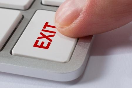 escape key: Finger is pressing EXIT key of a modern stylish aluminium white computer keyboard