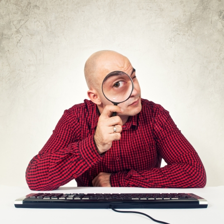 internet search: Bald yopung adult man sitting at the table with keyboard holding magnifying glass in front of the computer, internet search concept