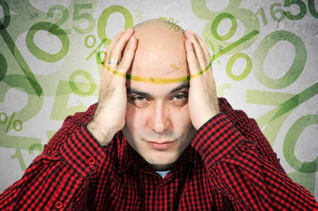 mortgage rates: Man having headache because of morgage rates, computer generated percentage signs fly around his head
