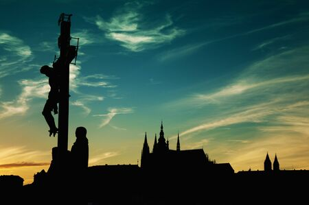 praha: 17th Century Crucifixion statue on Charles Bridge in Prague, Czech Republich. Image is taken against the light in the sunset.