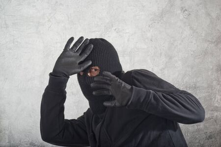 criminality: Catch the burglar concept, thief with balaclava caught in front of the grunge concrete wall.