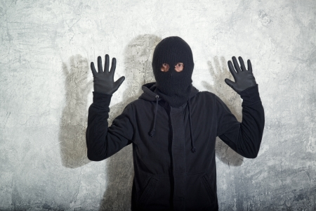 shoplifter: Catch the burglar concept, thief with balaclava caught in front of the grunge concrete wall.