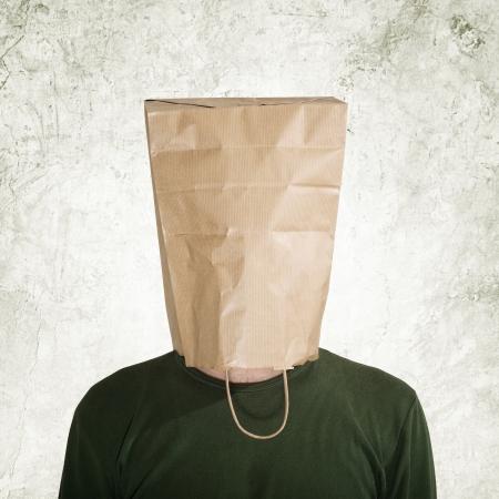 avergonzado: cabeza en la bolsa de papel, bolsa hombre escondido detrás de theshopping. Foto de archivo