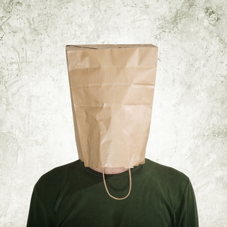 testa nel sacchetto di carta, l'uomo nascosto dietro borsa theshopping. Archivio Fotografico