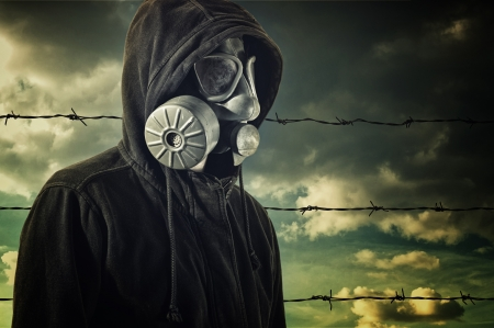 Man in dark clothes wearing a classic gas mask respirator in front of barb wire fence photo