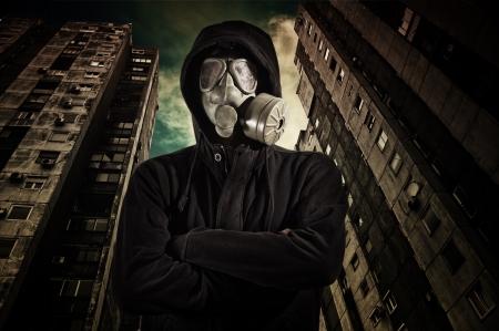 mascara de gas: Hombre en ropa oscura que llevaba un respirador gas mask clásico