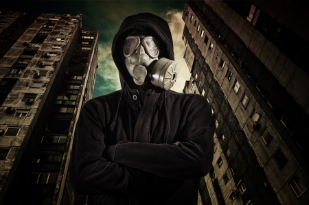 Man in dark clothes wearing a classic gas mask respirator photo