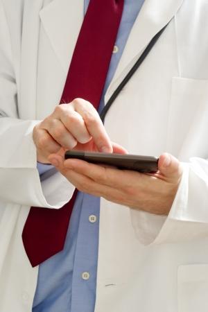 male doctor: Maschio medico in camice bianco sta usando un dispositivo moderno smartphone con schermo tocuh.