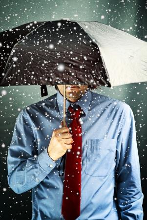 wirtschaftskrise: Gesch�ftsmann mit schwarzen Regenschirm sch�tzt sich vor dem Sturm. Finanzielles Problem, Wirtschaftskrise, harte Zeiten Konzept.