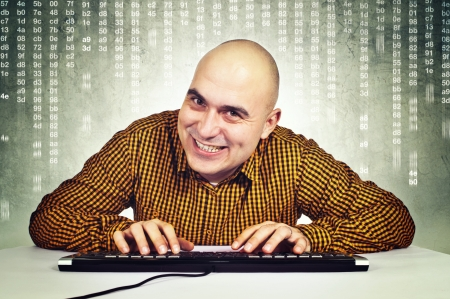 brak: Bald yopung adult male computer hacker sitting at the table with keyboard in front of the monitor