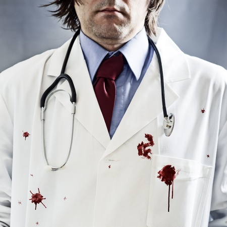 male killer: Killer doctor concept  Male doctor with stethoscope in white coat with red bloody stains over it and very dramatic side light and harsh shadows  Stock Photo