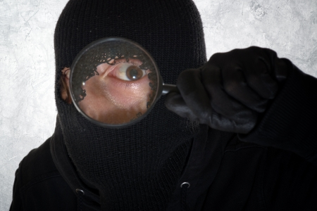 Burglar concept, thief with balaclava holding magnifying glass Stock Photo - 17749726
