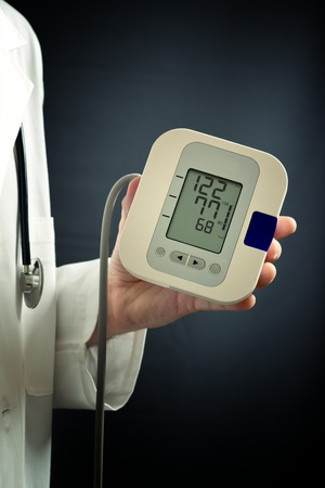 sphygmomanometer: Male doctor holding a digital blood pressure meter device in his left hand  Figures on led display show regular values common for normal blood pressure of a healthy person