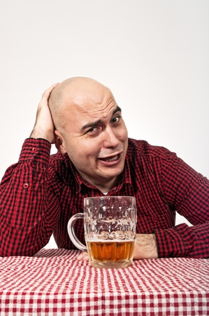Young adult bald man drinks beer from a jug photo