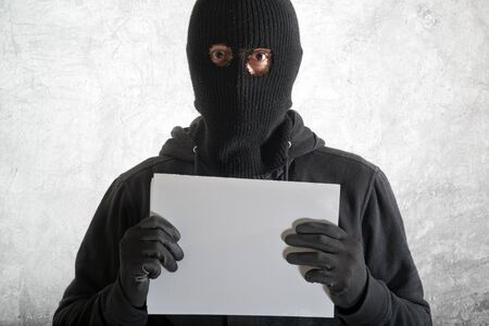 Arrested burglar concept, thief with balaclava caught and arrested in front of the grunge concrete wall Stock Photo - 17781004