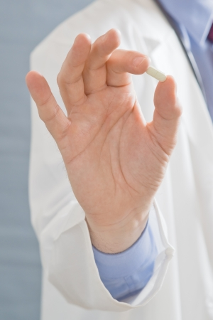Male doctor holding a pill, close up image with shallow depth of filed with focus on hand with a cure. photo