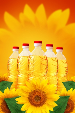 Sunflower oil in plastic bottles over a warm, sunny background, sunflowers scattered around. Stock Photo