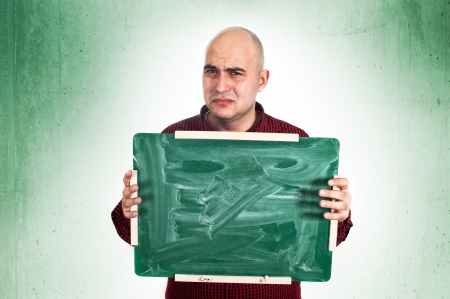 Sad bald young adult man holdinga small green chalkboard. photo