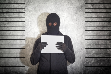 Arrested burglar concept, thief with balaclava caught and arrested in front of the grunge concrete wall. Stock Photo - 17922111