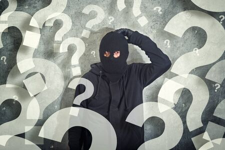 shoplifter: Confused burglar concept with lot of questions, thief with balaclava caught confused and without idea in front of the grunge concrete wall, computer generated question marks around him