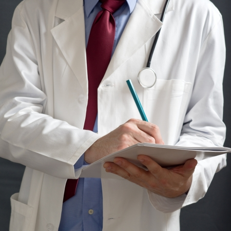 health professionals: Male doctor in white coat is writing notes in white notebook.