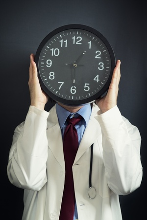 doctor burnout: Doctor is working overtime, holding a black clock in front pf his head. Overtime work, not enough time, time pressure, deadline concept. Stock Photo
