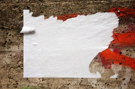 a public notice: Blank torn paper poster on an old brick wall