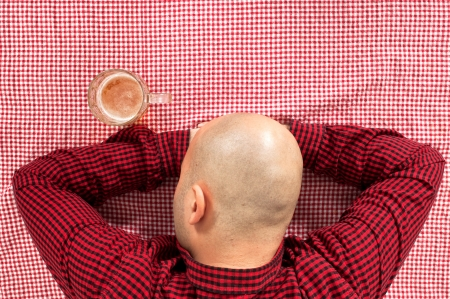 drinker: Bald beer drinker sitting in the bar with a glass of cold lager on the table  Stock Photo