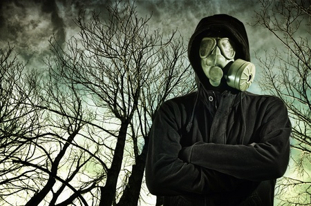 Man in dark clothes wearing a classic gas mask respirator, tree branches in the background. photo