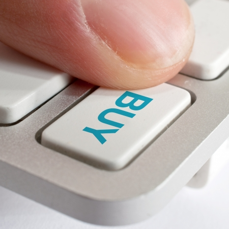 Finger pressing a computer keyboard key with word Buy. Stock Photo - 18256803
