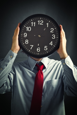 impatient: Businessman with black clock in front of his head, deadline concept. Not enough time to finish the job.