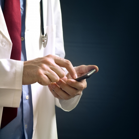 Male doctor in white coat is using a modern smartphone device with tocuh screen. photo