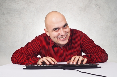 pervert: Bald yopung adult man sitting at the table with keyboard in front of the computer Stock Photo