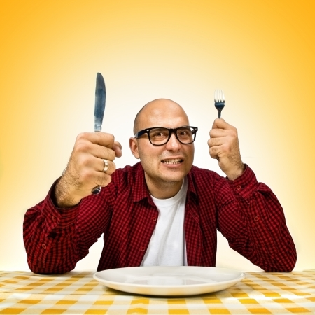 Young adult bold man sitting at the dinner table with fork and knife raised. photo