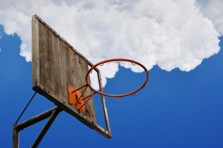 Street basketball. Old basketball hoop and a back board against blue sky with clouds photo