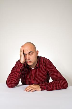 bald man: Preocupado joven adulto hombre calvo sentado a la mesa con la mano en la cabeza. Foto de archivo