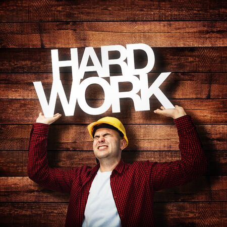 hardworker: Construction worker in red shirt and yellow hardhat, hard work concept