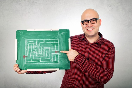 Bald young adult man with glasses holding a small green chalkboard with labyrinth showing the right way. photo