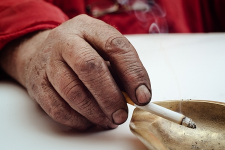 habbit: Dirty male hand holding smoking cigarette in an ashtray. Stock Photo