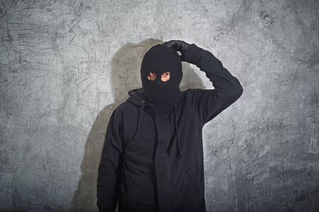 jailed: Confused burglar concept, thief with balaclava caught and arrested in front of the grunge concrete wall.
