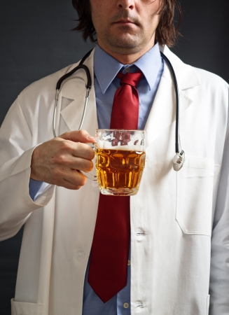 nutritive: Male doctor is drinking light beer from the glass jug. One glass of beer a day concept. Stock Photo