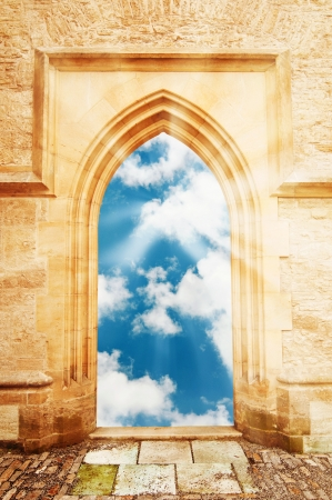 Arch door opening to a beautiful cloudy sky with sun rays photo